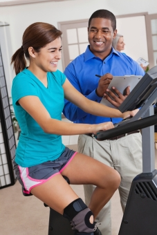 Physical therapist helping teen patient with therapy on exercise bike